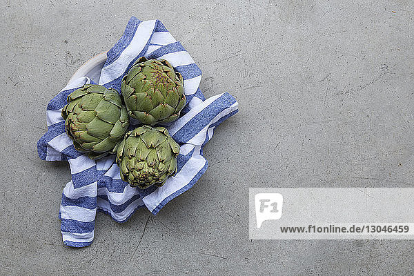 High angle view of healthy artichokes on table