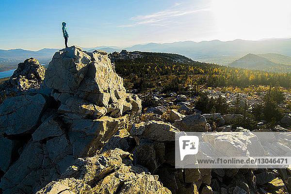 Wanderer steht auf Felsformation gegen den Himmel
