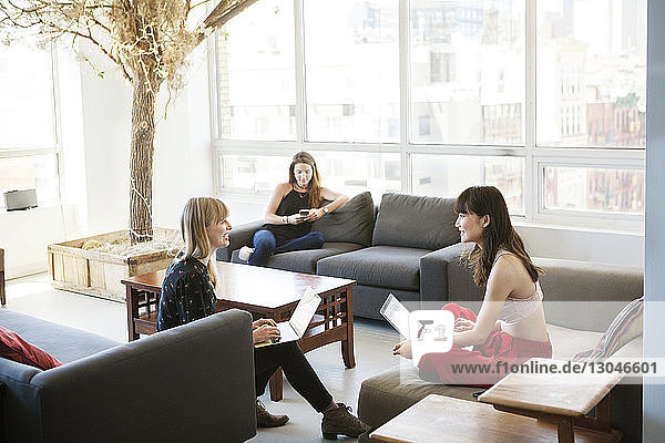 Businesswomen discussing while colleague using phone in background