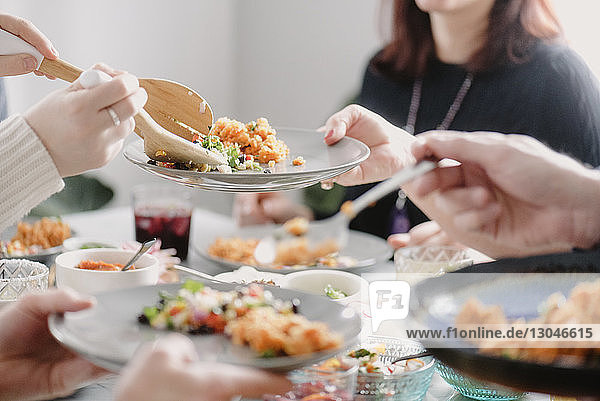Midsection of woman having lunch with friends at dining table