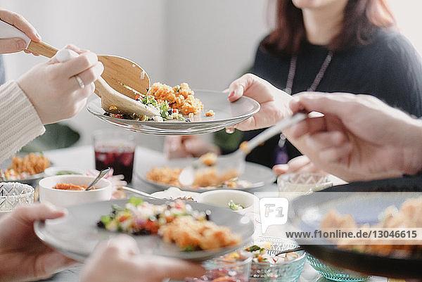 Mittelteil einer Frau beim Mittagessen mit Freunden am Esstisch