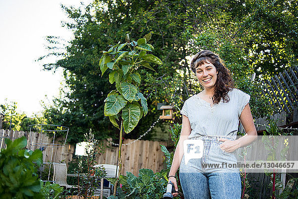 Low angle view of happy woman standing in garden at yard