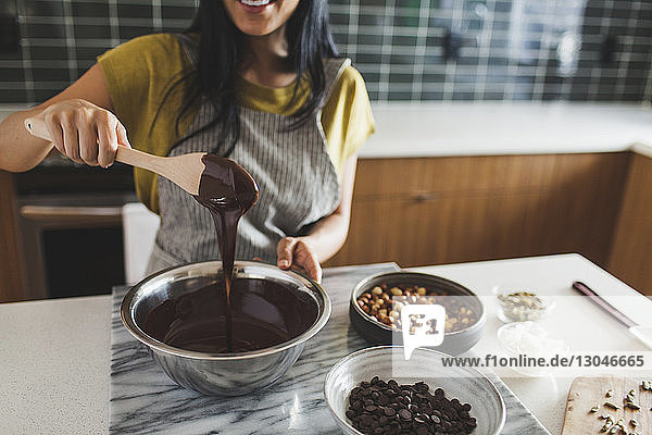 Midsection of woman making chocolate sauce in kitchen