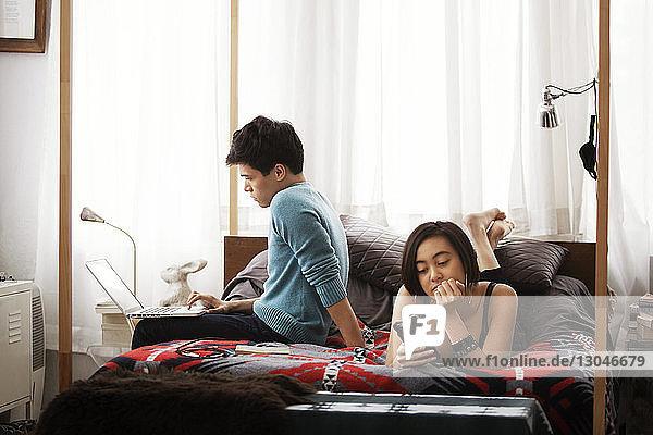 Ehepaar benutzt Laptop und Smartphone im Schlafzimmer