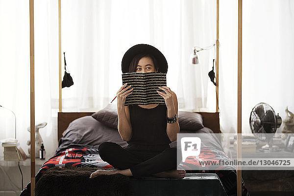 Glückliche Frau versteckt Gesicht mit Buch  während sie zu Hause auf dem Bett sitzt