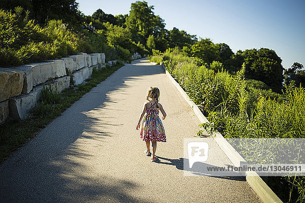 Rear view of girl walking on footpath amidst plants