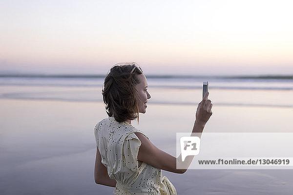 Seitenansicht einer glücklichen Frau  die mit einem Smartphone fotografiert  während sie am Strand gegen den Himmel steht