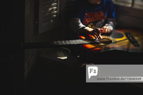Niedriger Teil eines Jungen  der zu Hause in der Dunkelkammer sitzt und Gitarre spielt