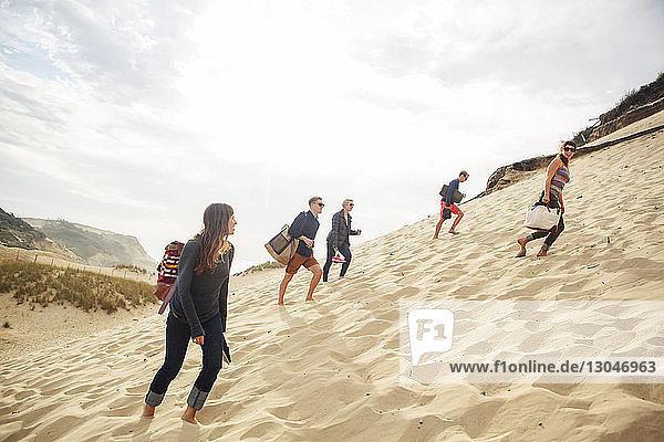 Freunde gehen auf Sanddünen gegen den Himmel