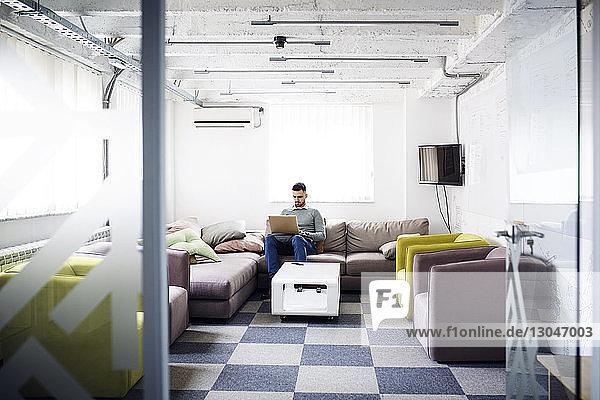 Geschäftsmann benutzt Laptop  während er in der Büro-Lobby auf der Couch sitzt