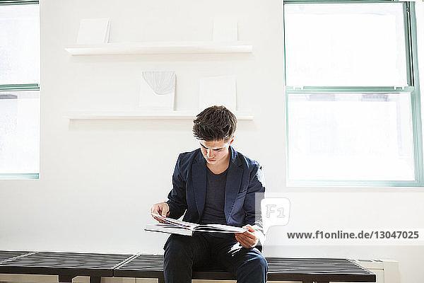 Geschäftsmann liest Buch  während er im Kreativbüro auf einer Bank sitzt Geschäftsmann liest Buch, während er im Kreativbüro auf einer Bank sitzt