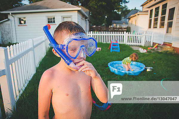 Brother wearing snorkel while sister playing in wading pool at yard