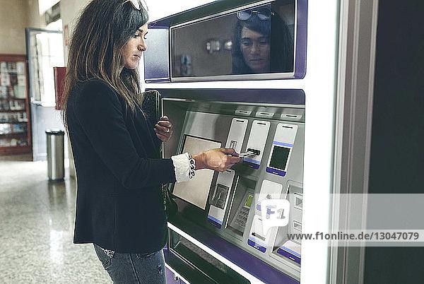 Frau schiebt Karte in Geldautomaten ein
