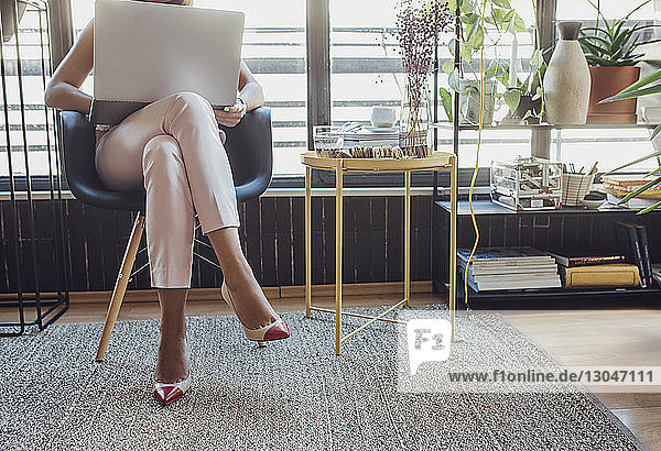 Low section of businesswoman using laptop computer while sitting on chair at home office