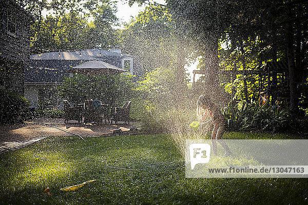 Happy girl in swimwear playing with sprinkler in backyard