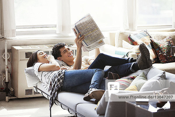 Happy couple reading newspaper while lying on sofa at home
