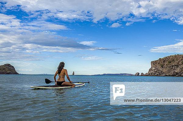 Frau sitzt auf einem Paddelbrett im Meer vor blauem Himmel
