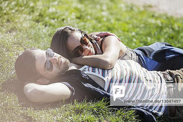 Romantisches Paar liegt im Sommer auf Gras