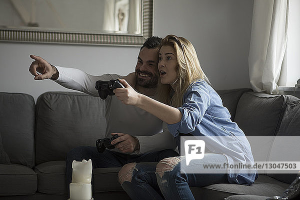 Happy couple playing video game while sitting on sofa at home