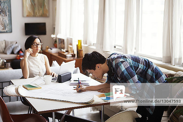 Man analyzing blueprint while woman sitting at home