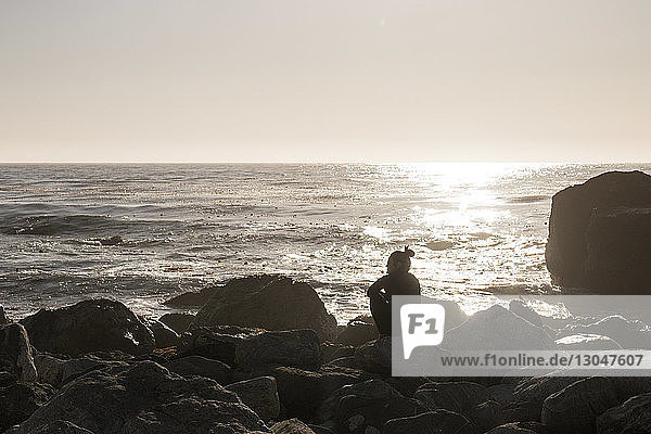 Rückansicht einer Frau  die bei Sonnenuntergang auf Felsen am Strand vor klarem Himmel sitzt