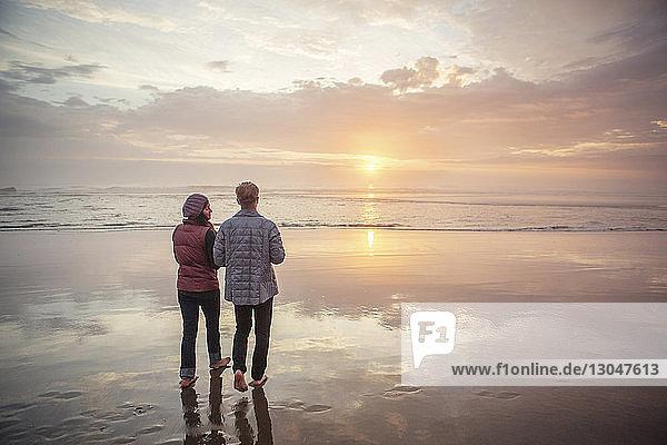 Rückansicht eines Paares  das bei Sonnenuntergang am Strand gegen den Himmel läuft