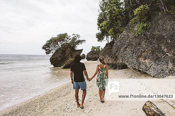 Rückansicht eines Paares  das sich beim Strandspaziergang an den Händen hält
