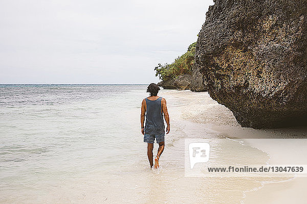 Rear view of man walking on shore against sky at beach
