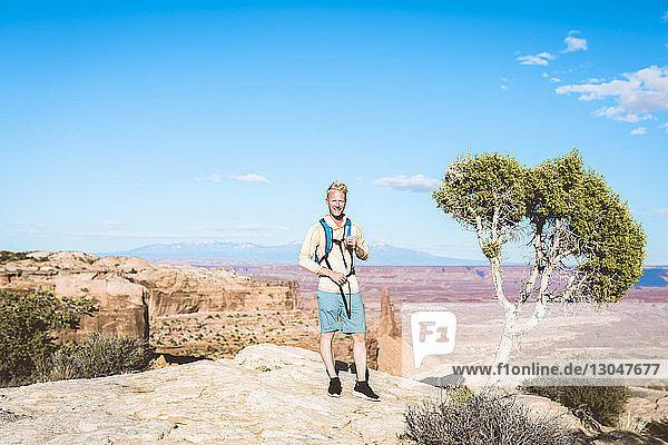 Porträt eines männlichen Wanderers  der auf einem Berg vor blauem Himmel steht