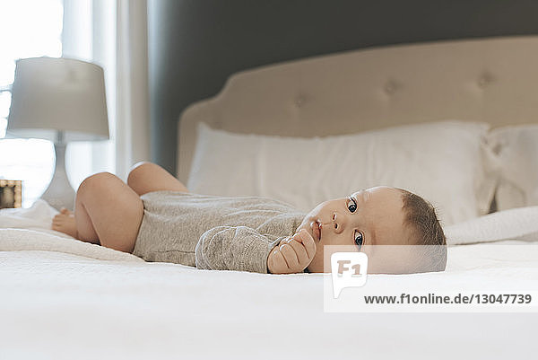 Portrait of baby boy lying on bed at home