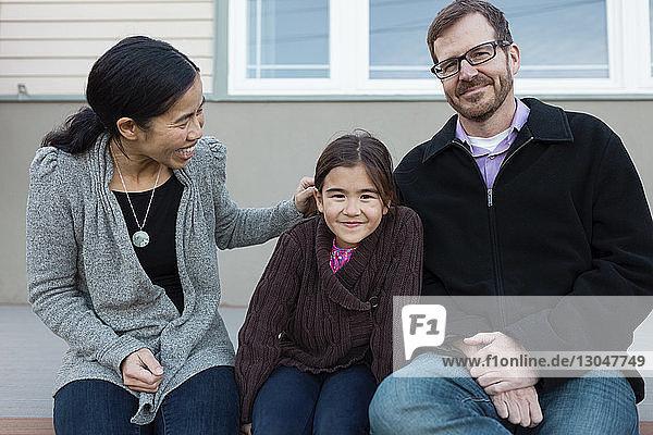 Glückliche Familie sitzt auf der Veranda