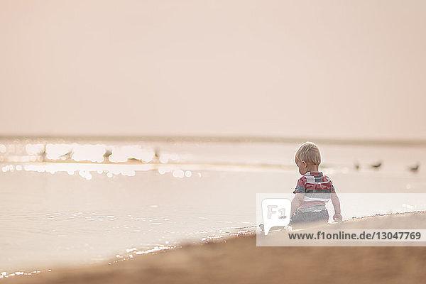 Rückansicht eines kleinen Jungen  der bei Sonnenuntergang am Strand gegen den Himmel sitzt