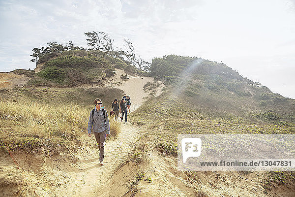 Freunde gehen im Sommer auf Berg gegen Himmel