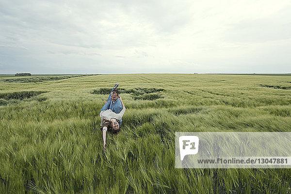 Mann trägt unbekümmerte Frau  während er im Grasfeld gegen den Himmel steht