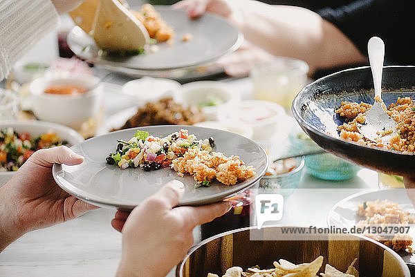 Cropped image of friends having food at dining table in party
