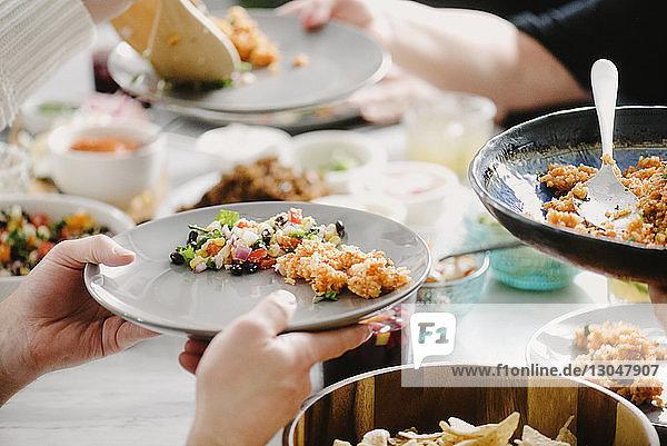 Ausgeschnittenes Bild von Freunden  die in einer Party am Esstisch essen