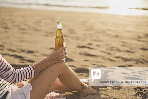 Niedriger Teil einer Frau  die beim Entspannen am Strand eine Bierflasche hält