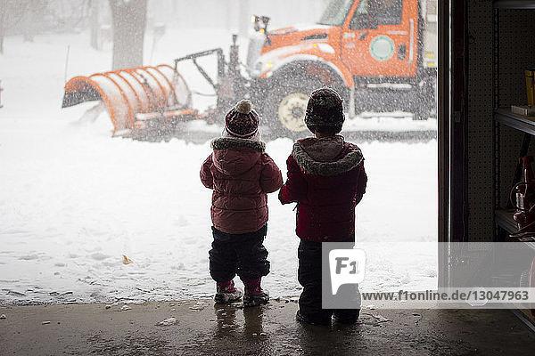 Rückansicht von Geschwistern in warmer Kleidung  die am Eingang des Geschäfts stehen
