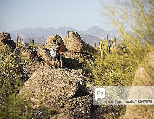 Ehepaar betrachtet die Aussicht  während es auf Felsformationen vor klarem Himmel steht