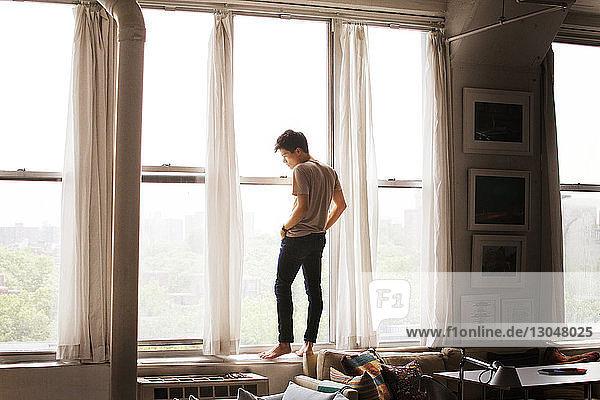 Nachdenklicher Mann steht zu Hause auf dem Fensterbrett