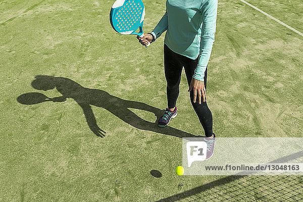 Niedriger Abschnitt einer Frau  die bei Sonnenschein Paddle-Tennis auf dem Platz spielt