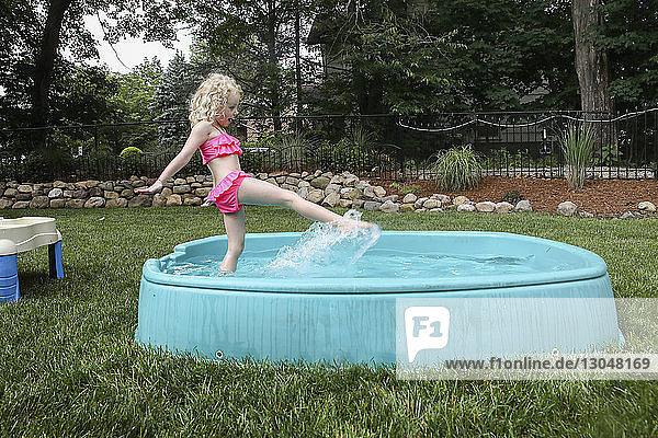 Seitenansicht eines Mädchens  das im Planschbecken auf dem Hof spielt