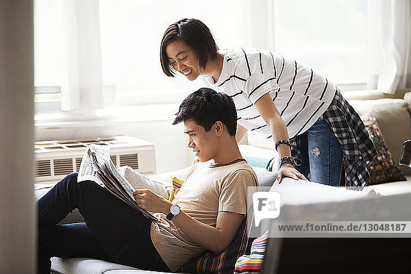 Happy couple reading newspaper in living room