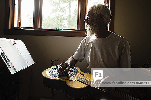 Senior man looking at papers while learning guitar against window at home