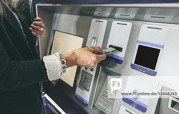 Mittelteil einer Frau beim Einführen der Karte in den Geldautomaten