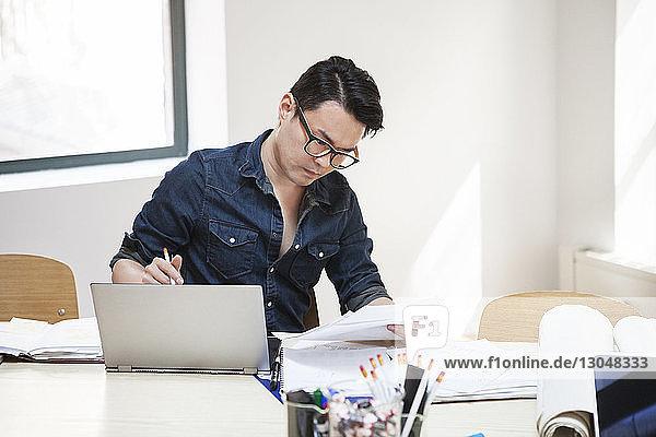Geschäftsmann liest Dokument  während er mit seinem Laptop am Schreibtisch im Kreativbüro sitzt Geschäftsmann liest Dokument, während er mit seinem Laptop am Schreibtisch im Kreativbüro sitzt