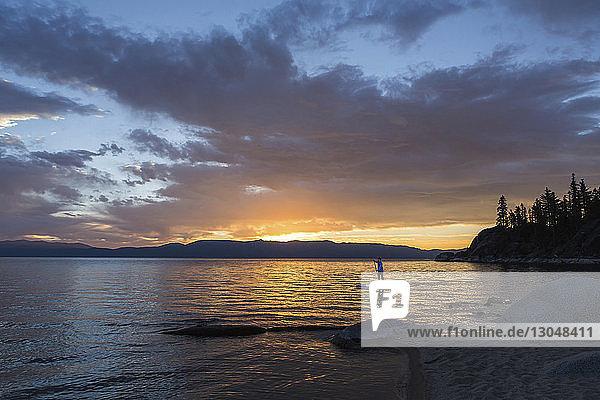 Mann paddelt im See gegen bewölkten Himmel bei Sonnenuntergang