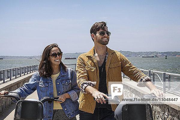 Glückliches Paar mit Fahrrädern geht am Beobachtungspunkt gegen den klaren Himmel