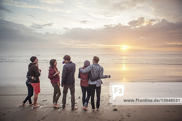 Couples standing on shore at beach during sunset