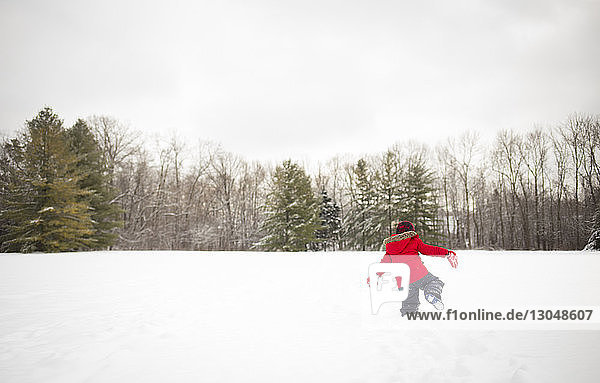 Rückansicht eines Jungen  der sich auf einem schneebedeckten Feld vergnügt